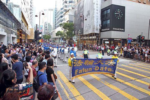 """'图6~11:法轮功学员游行庆祝""""世界法轮大法日"""",及""""法轮大法弘传世界二十五周年""""纪念,吸引香港市民及中西游客驻足关注及拍照。'"""