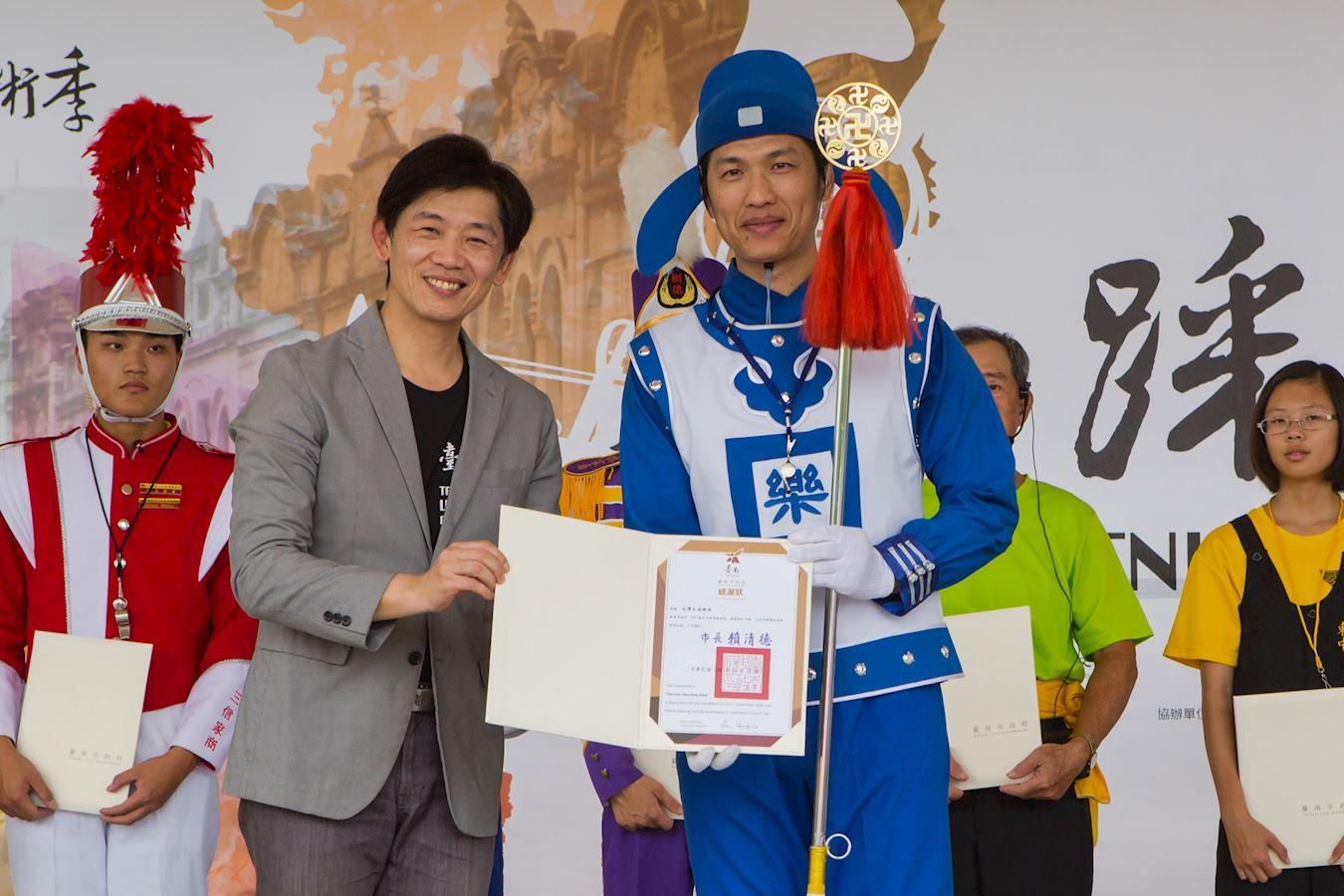 """台南市文化局长叶泽山说:""""感谢参加的乐团为提升台南的音乐文化、活络地方艺文发展所作贡献。""""并颁感谢状给法轮大法天国乐团。(明慧网)"""