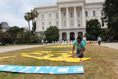"""'图1:二零一七年六月七日,法轮功学员们在州政府大楼南门外设置了图片展和摆放了""""真、善、忍""""三个大字,向到这里的各界人士介绍法轮功。并让了解真相的民众,在""""真、善、忍""""上放一朵精美的纸折小莲花以表支持。'"""