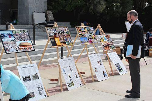 '图4:这位男士关注阅读真相展板上的照片和介绍法轮功的内容。'