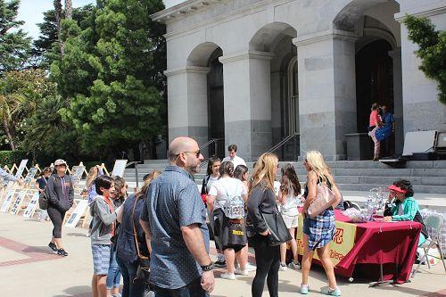 '图7~8:一批接一批前来参观州政府大楼的学生们驻足在真相桌前了解法轮功真相。'