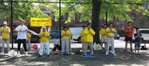 '图1:二零一七年六月十一日,纽约部份法轮功学员来到布鲁克林第三华人社区,向当地民众介绍法轮功。图为法轮功学员向过往民众展示法轮功功法。'