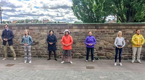 '图1,法轮功学员在斯德哥尔摩市政厅大门口的真相点前展示<span class='voca' kid='86'>功法</span>'