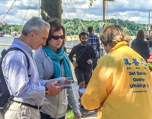 '图2,法轮功学员在斯德哥尔摩市政厅前向来自世界各地的游客讲真相'
