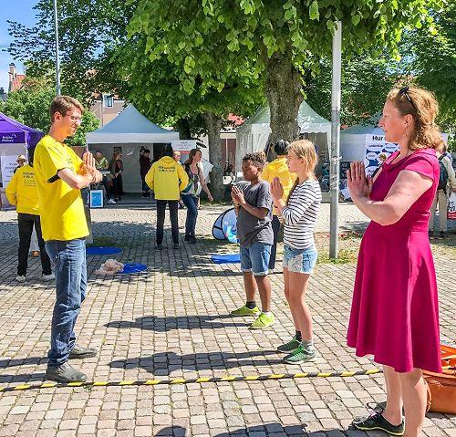 '图4:来参加瑞典榆树谷公园周的人们正在仔细阅读展板,了解法轮功真相。'