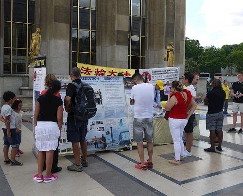'图1~2:巴黎人权广场上,游人驻足了解法轮功真相'