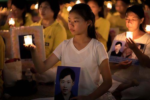 图4:来自辽宁的十六岁女孩徐鑫洋手捧父亲徐大为的遗像。徐大为因为坚持修炼法轮功被中共冤判八年监禁,出狱后十三天离世。