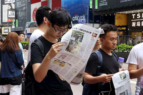 '图15~16:游客接获《明慧周报》等真相资料,欢天喜地的与游行队伍合照,有的迫不及待的阅读起来。'
