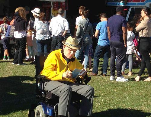 '图9:二零一七年六月二十五日,在东芬诗丽节上,坐在轮椅上的老人麦克(Mike)认真阅读真相传单并签名反迫害。'