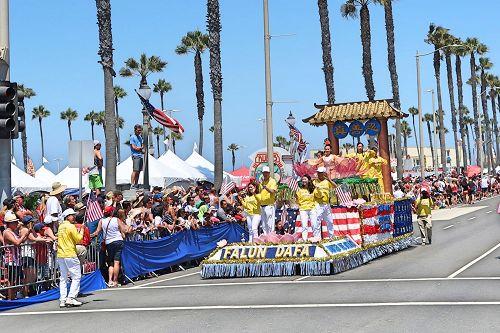 '图1~4:二零一七年七月四日,洛杉矶法轮功学员参加了美国西部最大规模的国庆游行,明亮的色彩、振奋人心的腰鼓表演、以及精美而具有内涵的花车,在游行队伍中特别吸引人。法轮大法队伍的花车再次获得第二名。'