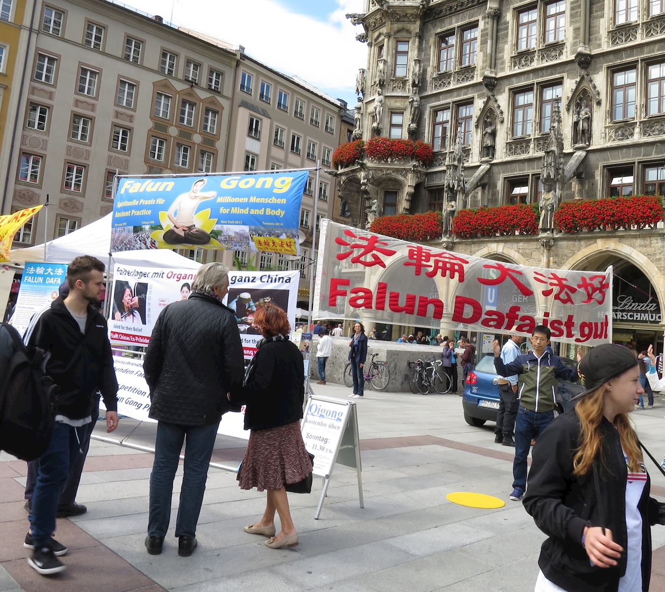 2017年8月12日,德國南部名城慕尼黑(Munich)部分法輪功學員在市政廳前瑪琳廣場(Marienplatz)設立法輪功真相展位。有人當場跟法輪功學員學煉功法,還有人馬上就到對面的書店訂購《轉法輪》書籍。民眾也紛紛加入譴責中共對法輪功學員迫害的行列中,人們在給聯合國人權委員會的請願書上簽名。(明慧網)