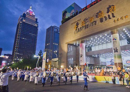 '图1~3:法轮功学员组成的天国乐团参加台北世大运的嘉年华踩街游行,整齐划一、精神抖擞行经台北市热闹的街头。'
