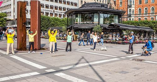 '图1:在瑞典文化节期间,法轮功学员在斯德哥尔摩的北城广场(Normalmstorget)设立真相点向民众介绍法轮大法的真相。图为学员们正在展示法轮功的第二套功法——法轮桩法。'