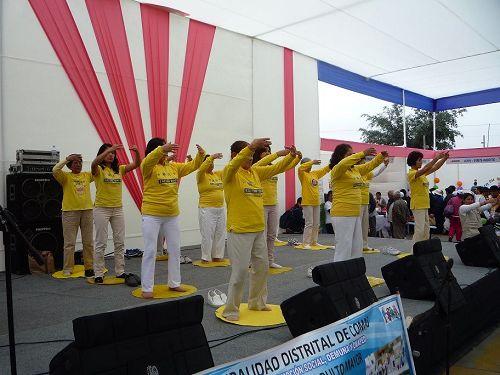 '图2~3:秘鲁法轮功学员在果玛斯的老人服务日社区活动上演示功法'