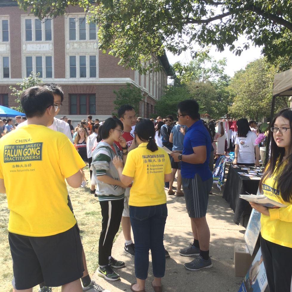 在伊大香槟分校社团招新活动上,身穿黄色衣服的法轮功学员向中国留学生讲述真相。(明慧网)