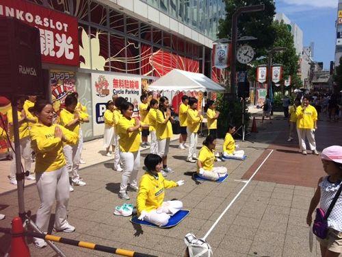 """'图8~9:八月六日(星期天)下午,法轮功学员们在四日市市近铁车站附近的""""第五十四届大四日市庆祝活动""""的广场上,表演了法轮功的五套功法。'"""