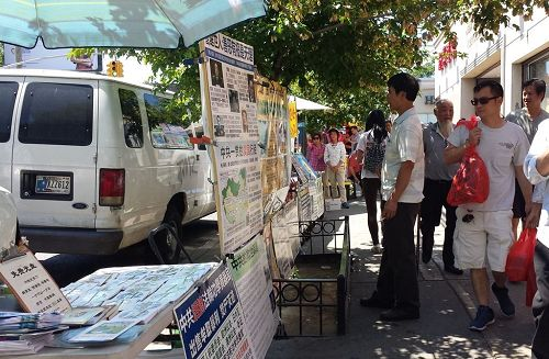 '圖3~5:法輪功學員在布魯克林「八大道」設立真相點,不少過往民眾經過時閱讀真相展板。'