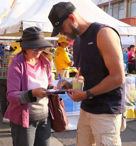 '年輕人馬特在征簽表上簽名支持反迫害。'