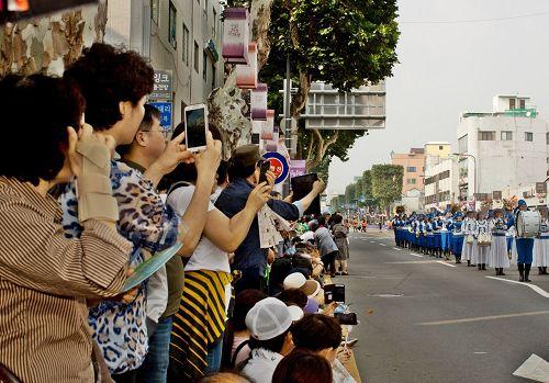 '图8:法轮功团体表演所到之处,都受到观众热情的鼓掌,观众们纷纷用手机拍照录像。'