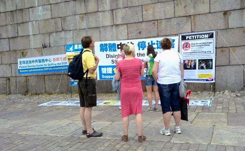 '图2:议会广场上,游客观看横幅,了解法轮功真相'