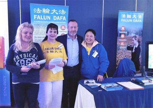 """'图1:在""""平衡健康展""""上,爱尔兰欧盟议员肖恩·凯里(SeanKelly)来到法轮功学员展位,与法轮功学员合影留念。'"""