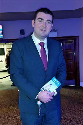 """'图2:1月14日爱尔兰西南部基拉尼""""平衡健康展""""上,爱尔兰体育部副部长布伦丹·格里芬(BrendanGriffin)在听取法轮功学员讲解后,高兴地收下了法轮功真相传单和莲花饰品。'"""