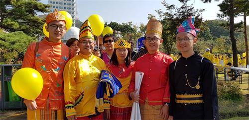 '图28:印尼法轮功学员黄义任全家身着民族服装参加游行'
