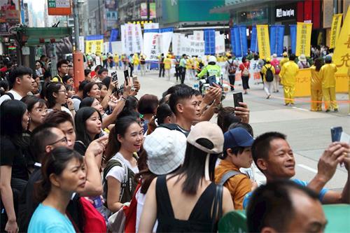 '图16:游行吸引沿路民众,许多人拿起手机拍摄盛况。'