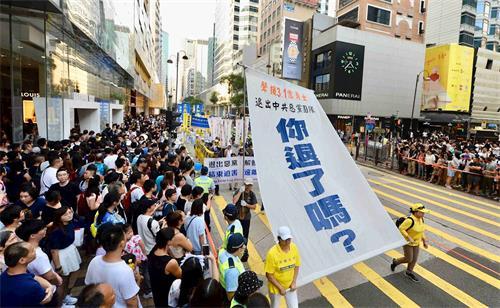 '图18:游行展示大型幡旗,呼吁中华儿女退出中共。'
