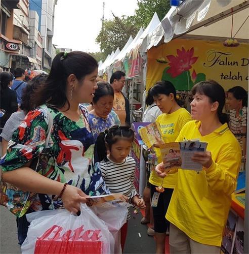 '图1:法轮功学员在文化节上向华人讲真相'