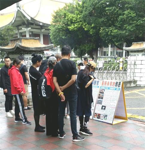 '图1~4:台北国父纪念馆前,大陆游客认真阅读法轮功真相展板'