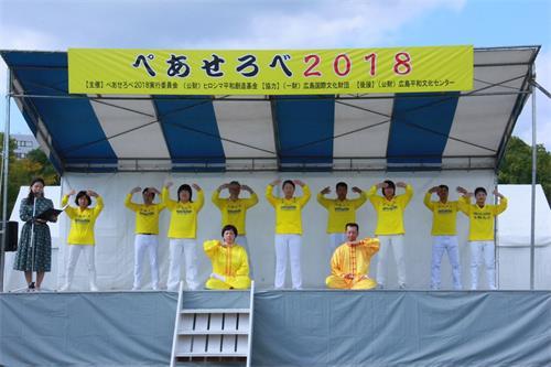 '图2:法轮功学员在和平与爱国际交流节舞台上演示五套<span class='voca' kid='86'>功法</span>动作'