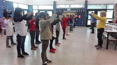 'Figura 1: el 31 de agosto de 2018, los practicantes de Falun Gong en Buenos Aires enseñaron a los niños ejercicios de Falun Gong en una escuela en la ciudad de Sorano.  '