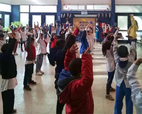 'Figuras 2 a 3: el 13 de julio de 2018, los practicantes de Falun Gong en Buenos Aires enseñaron a los niños ejercicios de Falun Gong en una escuela en la ciudad de Sorano.  '