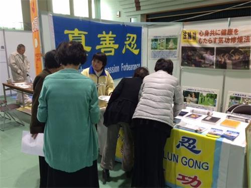 '图1~2:日本法轮功学员参加了在银杏黄叶节上和民众讲述法轮功真相'