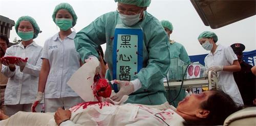 图1:法轮功学员在模拟中共活摘器官,揭露中共邪恶。