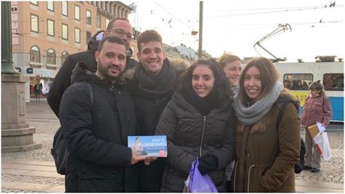 '图2:来自西班牙的旅游者手持法轮功真相传单合影,表示支持法轮功反迫害'