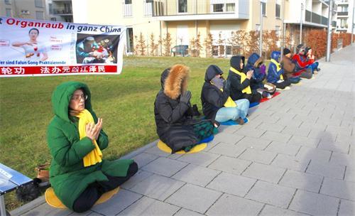 '图4:二零一八年十二月八日,来自德国和奥地利的法轮功学员在的德国慕尼黑中领馆对面举办活动,制止中共迫害法轮功。'