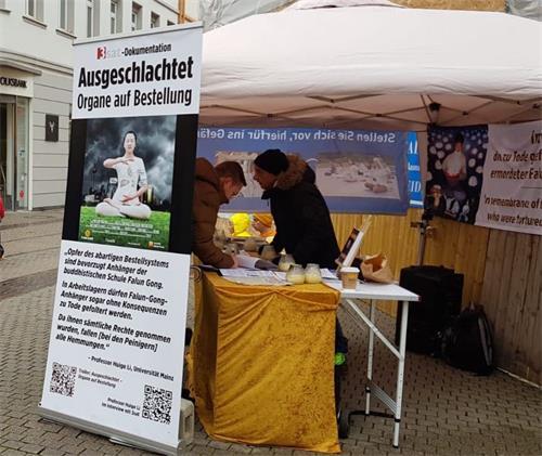 '图5:法轮功学员在海德堡主街与剧院大道交汇处举办活动,民众签名声援。'