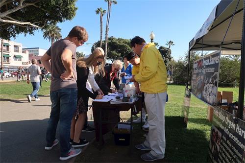 '图8:圣莫妮卡海滩公园的游客签署停止活摘器官的请愿书。'