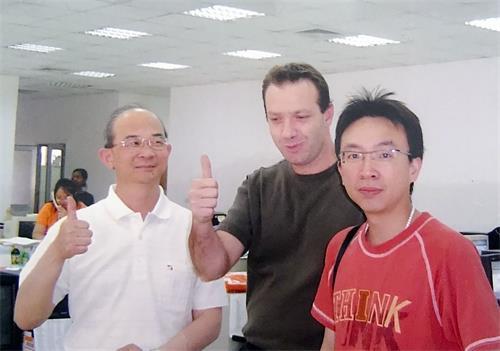 ''图3:黄士坤(左)修炼大法之后,如期于二零零四年在赖索托建厂时,与来访的美国客户的合照。''