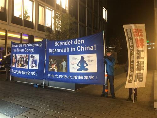 '图:二零一八年十一月二十六日晚,法轮功学员在汉堡市中心,经济峰会举办招待会的Esplanade街上,竖立起有夜间照明灯的大型彩色横幅,希望能引起人们关注正在中国发生的活摘器官罪行。'