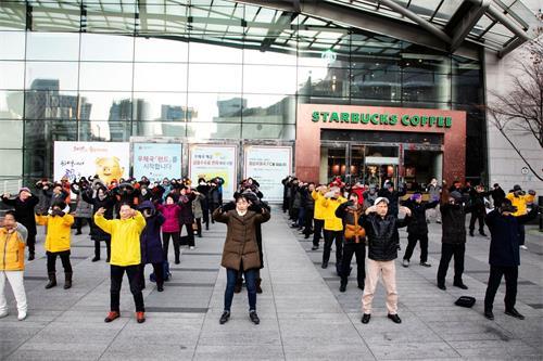 '图1:韩国法轮功学员在首尔市中心明洞中央邮局前炼功,场面祥和,吸引韩国民众与各国游客驻足观赏。'