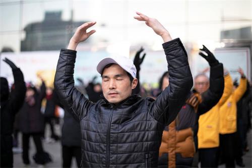 '图2:韩国法轮功学员在首尔市中心明洞中央邮局前炼法轮<span class='voca' kid='53'>大法</span>的第二套<span class='voca' kid='86'>功法</span>-法轮桩法。'