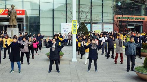 '图1~7:二零一八年十二月二十五日圣诞节,韩国法轮功学员在首尔市中心明洞中央邮局前炼功,场面祥和,吸引韩国民众与各国游客驻足观赏。'
