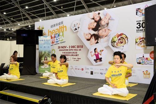 '图2~3:新加坡法轮功学员登台向参展民众展示平静祥和的五套功法'