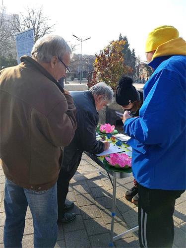'图2:民众在要求法办江泽民的征签表上签名'
