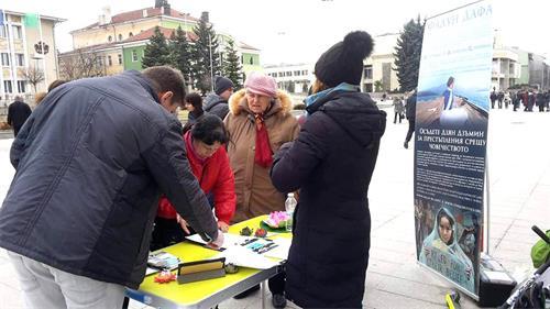 '图3:民众在要求法办江泽民的征签表上签名'