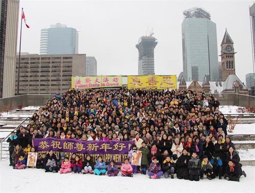 '图1~2:中国新年即将来临之际,多伦多法轮功学员聚集市政厅前给慈悲伟大的师父拜年,恭祝师父新年好!'