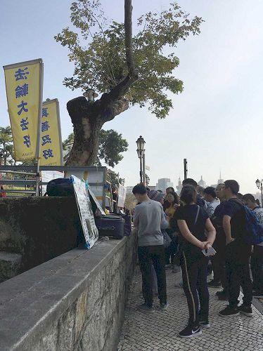 '图1~4:中国大陆游客在澳门景点认真阅读法轮功真相展板'
